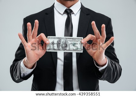 Closeup of businessman in suit and tie holding one hundred dollars banknote over white background - stock photo