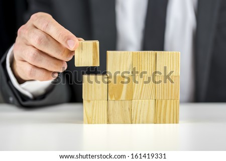 Closeup of businessman making a structure with wooden cubes. Building a business concept. - stock photo