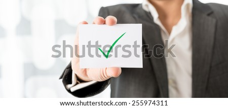 Closeup of businessman or teacher holding up a white card with green check mark. Conceptual of successfully completed task or homework. - stock photo