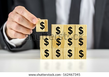 Closeup of businessman putting together many wooden cubes with dollar sign on them.  - stock photo