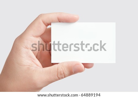 Closeup of businessman's hand holding blank white paper business card for your message (copy space), isolated on gray background - stock photo