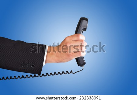 Closeup of businessman's hand holding telephone receiver against blue background - stock photo