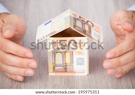 Closeup of businessman's hands protecting euro house on table - stock photo