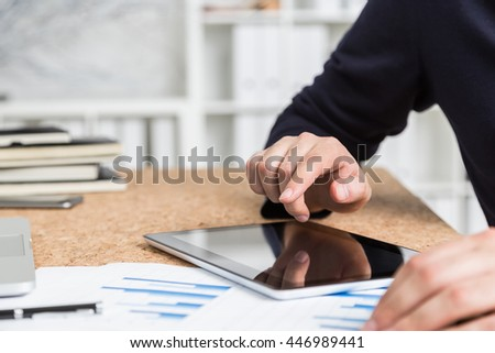 Closeup of businessman's hands using tablet on cork desktop with paperwork, pen and laptop