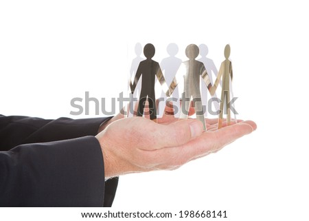Closeup of businessman's hands with paper people representing unity over white background - stock photo