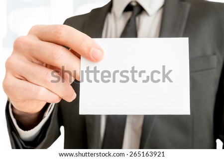 Closeup of businessman showing blank white business card with copy space ready for contact info or other company information. - stock photo