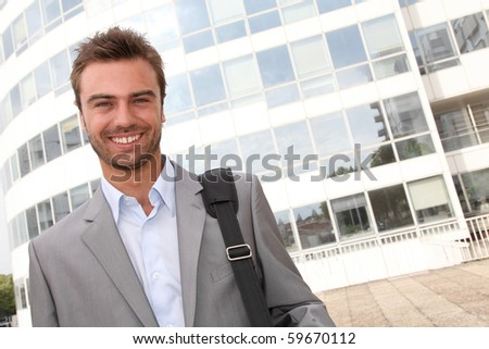 Closeup of businessman standing in front of offices building - stock photo