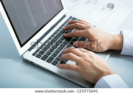 Closeup of businessman typing on laptop computer - stock photo