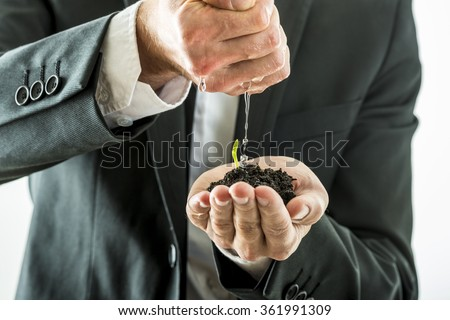 Closeup of businessman watering and nurturing a green sprout growing from a fertile soil he is holding in his cupped hand. Conceptual of business vision and start up.