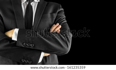 Closeup of businessman with arms crossed. Over black background.