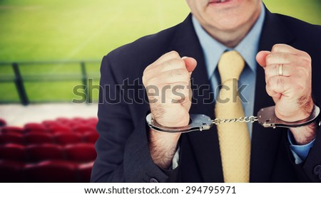 Closeup of businessman with handcuffed hands against red bleachers looking down on football pitch - stock photo