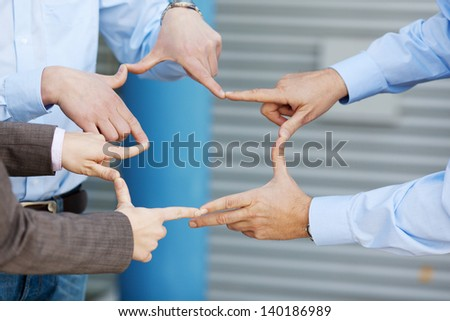 Closeup of businessmen and businesswoman joining fingers