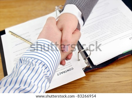 Closeup of businessmen and businesswoman shaking hands over the signed contract. - stock photo