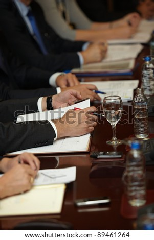 closeup of businesspeople hands during conference meeting - stock photo