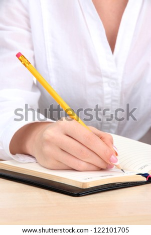 Closeup of businesswoman hand, writing on paper - stock photo