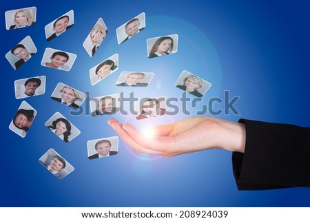 Closeup of businesswoman's hand with photographs over blue background - stock photo