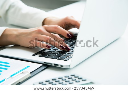 Closeup of businesswoman typing on laptop computer - stock photo