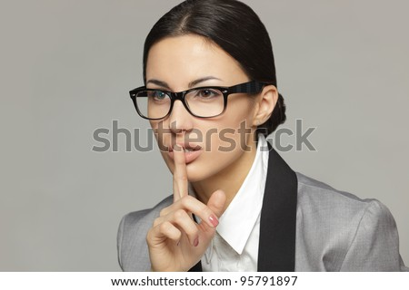 Closeup of businesswoman with finger on lips over grey background