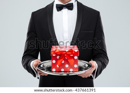 Closeup of butler in tuxedo holding tray with gift box - stock photo