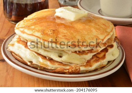 Closeup of buttermilk pancakes with melted butter and syrup