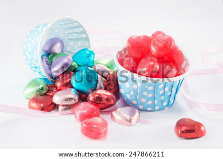 Closeup of Candy, Foil wrapped chocolate hearts, Ribbon, Valentines hearts on a white background  - stock photo