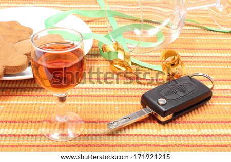 Closeup of car key with glass of wine lying on table after party, car key and alcohol, don't drink and drive concept - stock photo