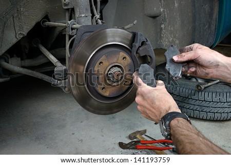 Closeup of car mechanic repairing brake pads - stock photo