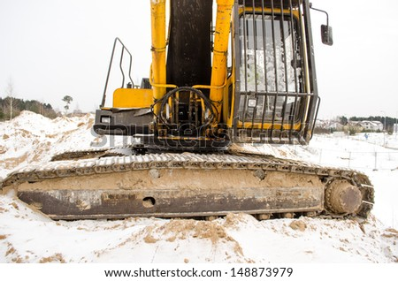 closeup of caterpillar excavator tractor driver cabin covered with snow in winter. heavy machinery industry.  - stock photo
