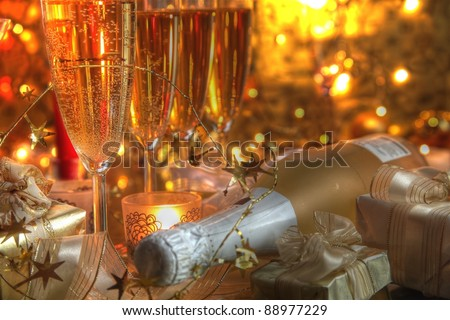 Closeup of champagne in glasses,bottle,gift boxes,candle lights  and twinkle lights on golden background.