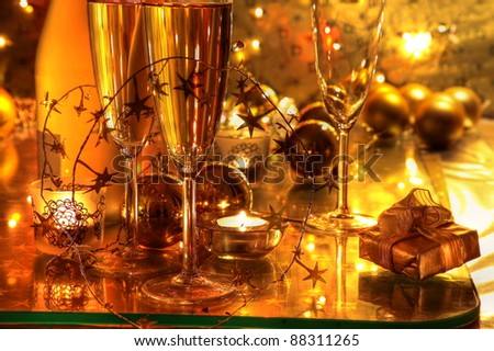Closeup of champagne in glasses, gift box, candle lights on golden background. - stock photo