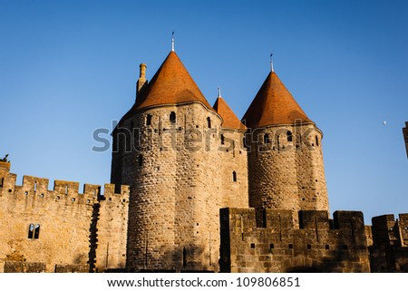 Closeup of Chateau Comtal towers with sun on their red tile roofs in Carcassonne, France. It is a UNESCO World Heritage Site medieval walled city known for its basilica, palace and towers. - stock photo