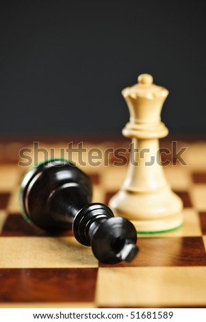 Closeup of checkmate on king by queen winning in chess game - stock photo
