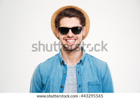 Closeup of cheerful young man in hat and sunglasses standing and smiling over white background - stock photo