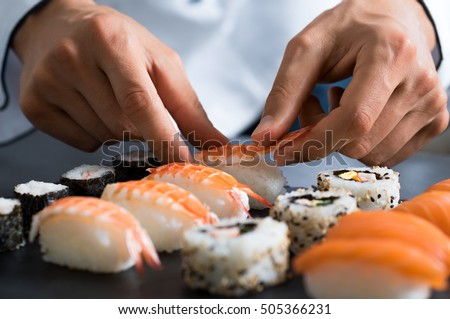 Closeup of chef hands preparing japanese food. Japanese chef making sushi at restaurant. Young chef serving traditional japanese sushi served on a black stone plate.