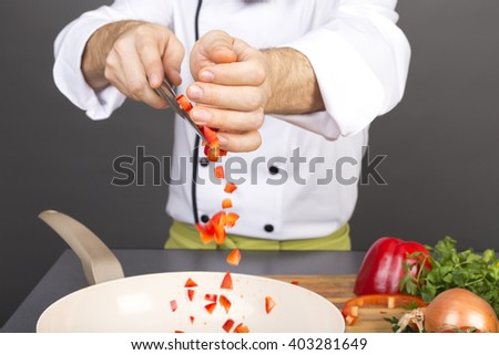 Closeup of chef hands putting chopped red pepper in a pan  - stock photo
