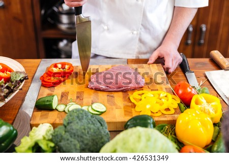 Closeup of cheif cook coooking meat and salad with fresh vegetables on the table - stock photo