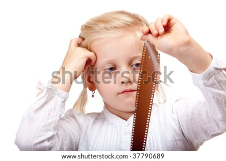 closeup of child looking at old analog camera film, isolated on white background - stock photo