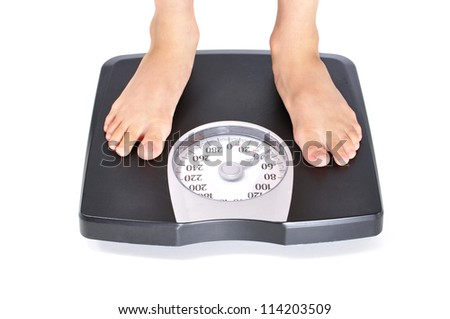 Closeup of child's feet standing on scale weighing forty pounds - stock photo