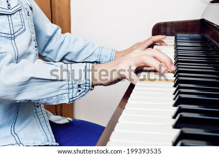 Closeup of child's hands playing piano - stock photo