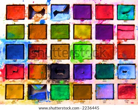 closeup of child's old tin toy paintbox with the brilliant colours of childhood - stock photo