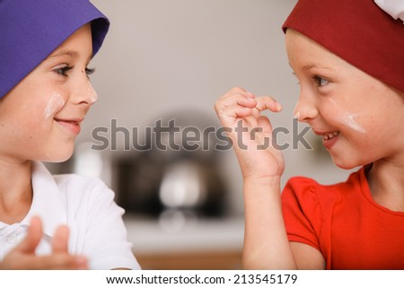 closeup of children making cakes and smiling. two kids having fun at kitchen table  - stock photo