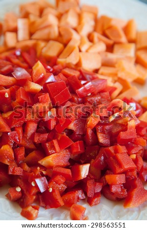 Closeup of chopped red sweet pepper with blurred carrots  - stock photo