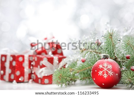 Closeup of Christmas ball with pine branch and gifts on abstract background. - stock photo