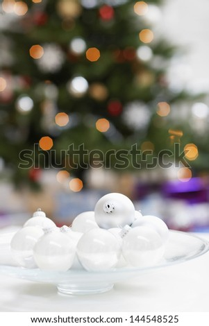 Closeup of Christmas baubles on plate with tree in background - stock photo