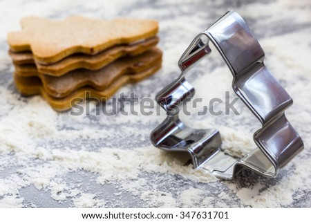 Closeup of christmas tree shaped pastry cutter with baked gingerbread cookies in the background. - stock photo