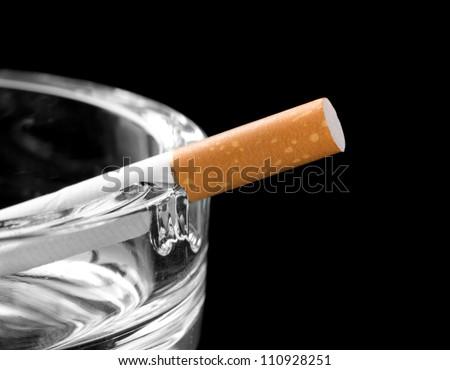 Closeup of cigarette on ashtray. Isolated on black - stock photo
