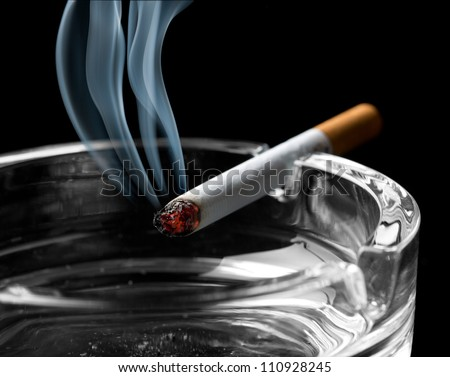 Closeup of cigarette on ashtray with a beautiful wisp of smoke - stock photo