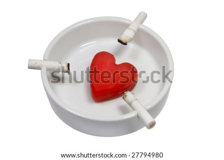 Closeup of cigarette stubs and a heart in a white ash-tray (symbolizing cardiovascular problems associated with smoking) - stock photo