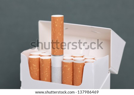 Closeup of cigarettes in a pack, one cigarette standing out