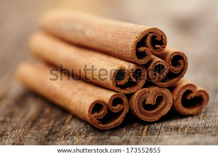 Closeup of cinnamon sticks with selective focus on a wooden board - stock photo